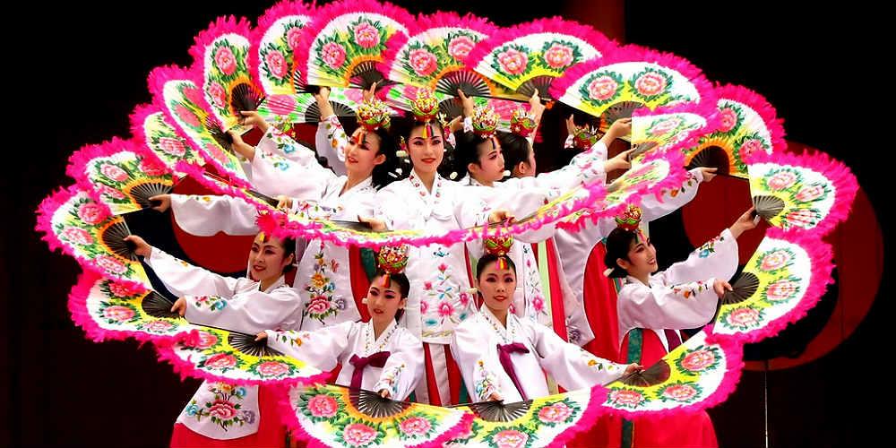 Ballerine coreane in cerchio con ventagli colorati.